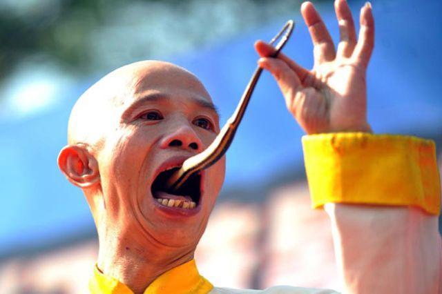 صيني يقف على مسمار براسه واخر يبتلع ثعبان