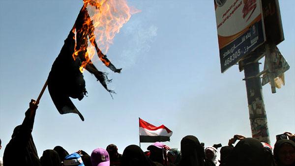 سيدة يمنية ترفع برقعا أحرقته احتجاجا على حكم صالح وسط صنعاء.